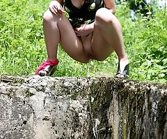Hot young ho pees over a dirty gutter in the park