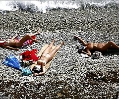 Three sexy ladies sunbathe nude right near the sea